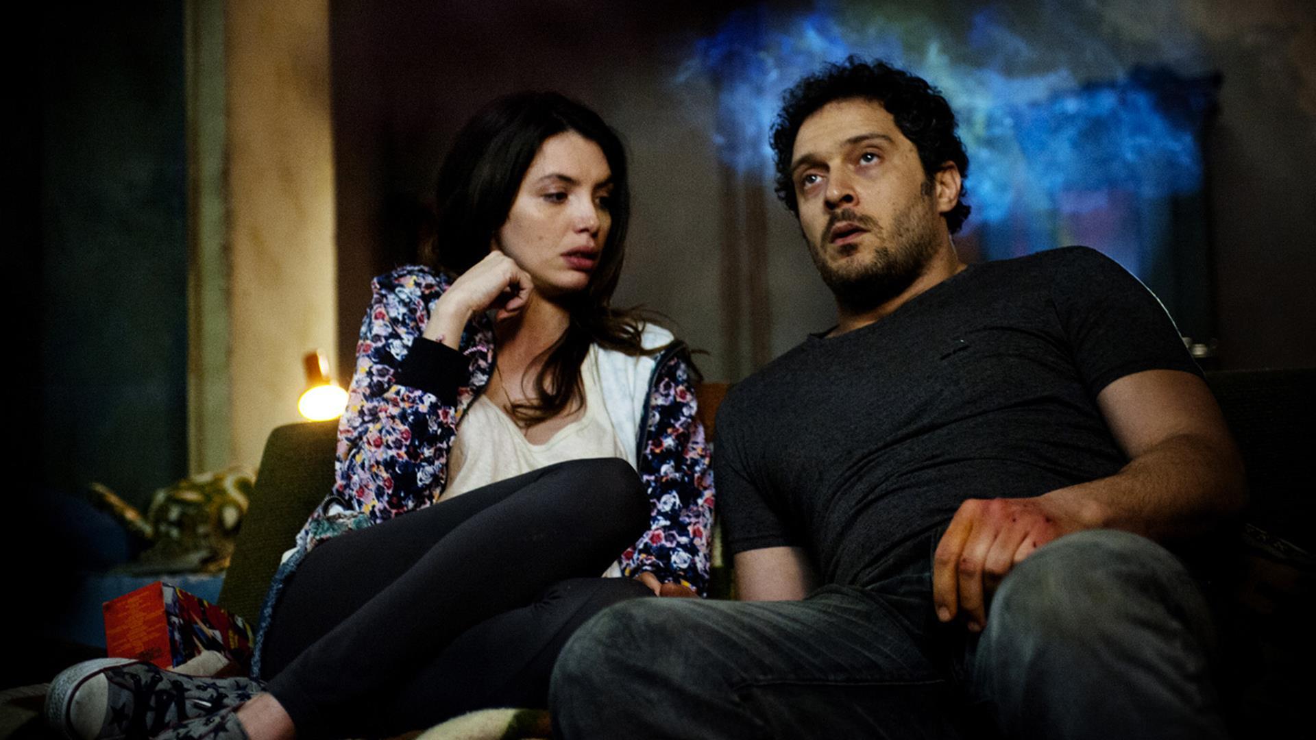 Claudio Santamaria ed Ilenia Pastorelli seduti su un divano in una scena di Lo Chiamavano Jeeg Robot di Gabriele Mainetti