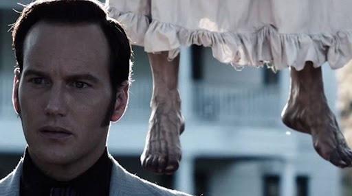 I piedi della strega impiccata alle spalle di Ed in una scena di The Conjuring