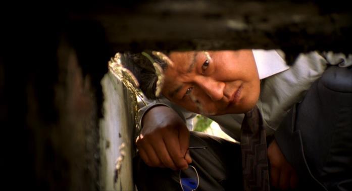 Il detective Park guarda nella canalina di scolo alla fine di Memorie di un assassin