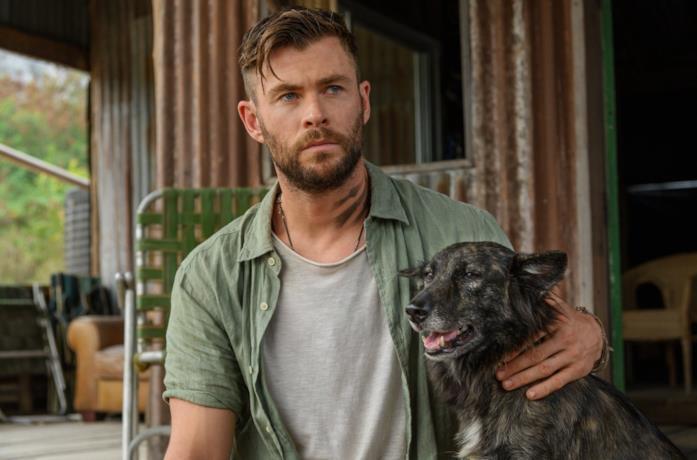 Chris Hemsworth accarezza il suo cane in una scena di Tyler Rake