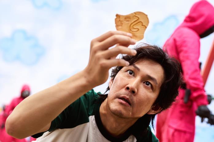 Gi-hun cerca di sciogliere il caramello in Squid Game