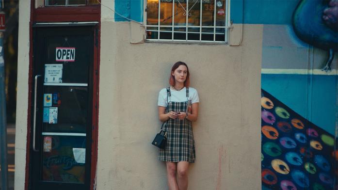 Lady Bird sola appoggiata al muro di un negozio