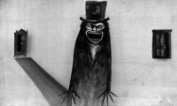 """Una pagina del libro """"Mr. Babadook"""" che raffigura il mostro, un'entità scura con un cilindro"""