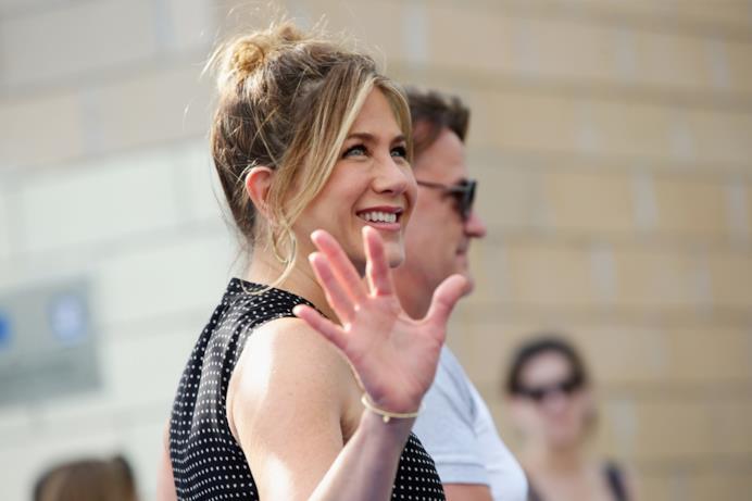 Jennifer Aniston sorridente saluta i fan sul blu carpet del Giffoni Film Fest