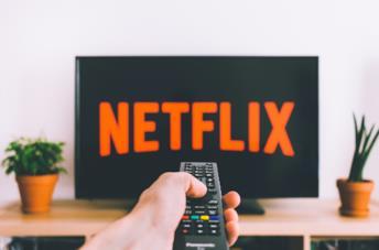 Il logo di Netflix in un televisore e un utente con un telecomando