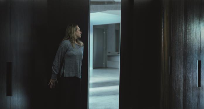 Elisabeth Moss nascosta contro una porta aperta