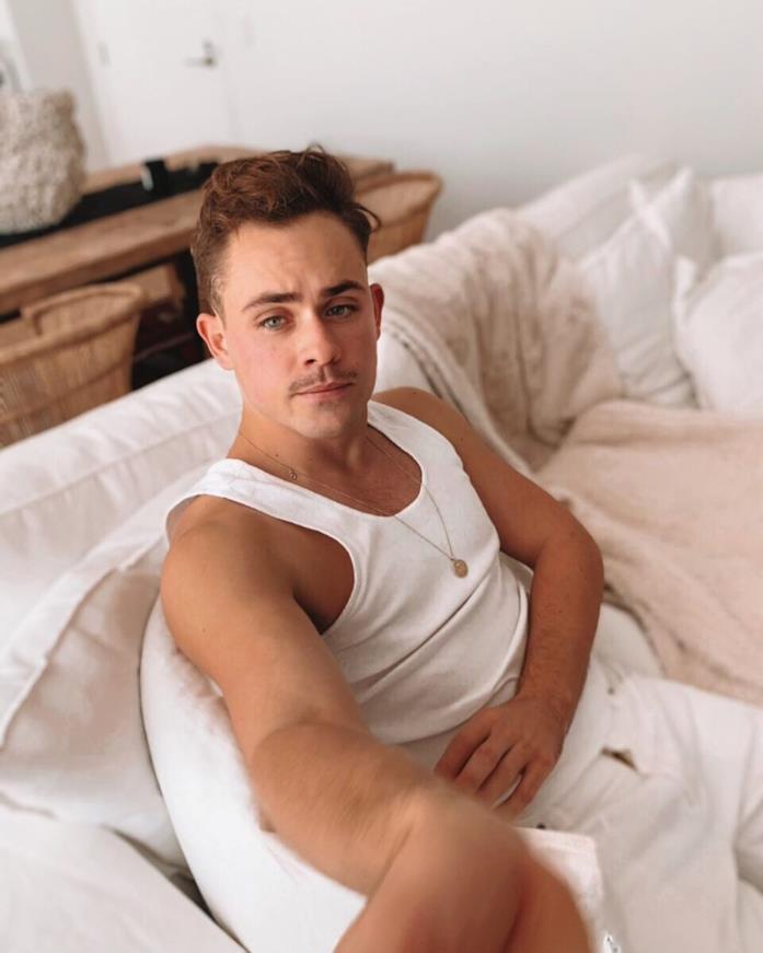 Dacre Montgomery in canottiera e pantaloni bianchi, seduto su un sofà