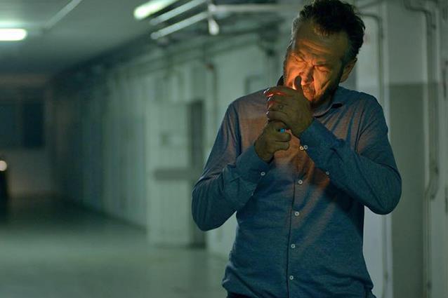 Rocco Schiavone si accende una sigarett