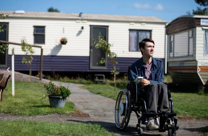 Isaac è seduto su una sedia a rotelle