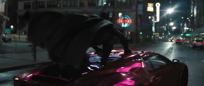 Batman di schiena accovacciato sul tettuccio di un'auto colorata