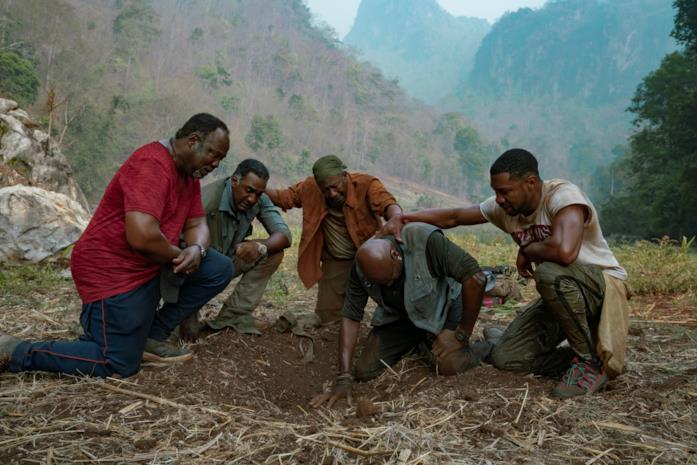 I 5 protagonisti inginocchiati presso la tomba di Norman