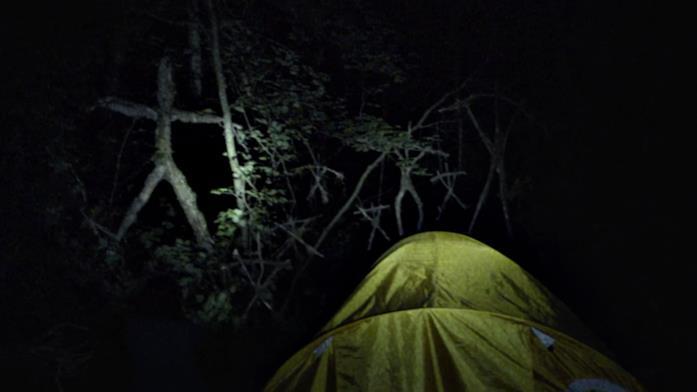 Una scena notturna di finto found footage con una persona di spalle di fronte ad un'inquietante scultura rudimentale di rametti