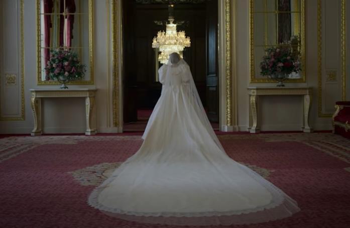 Lady Diana Spencer, con un abito bianco, cammina all'interno della lussuosa residenza