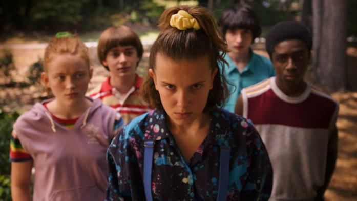 Un primo piano di Millie Bobby Brown assieme a parte del cast di Stranger Things 3