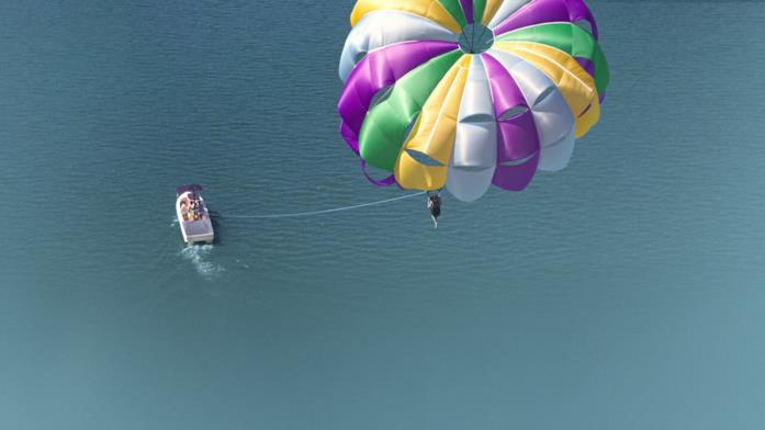 Una scena di parasailing inquadrata dall'alto, su un mare limpido.