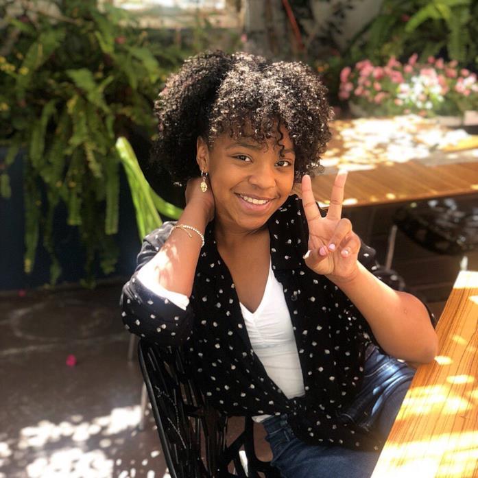 Priah Ferguson seduta a un tavolo sotto il sole, che fa il gesto della vittoria
