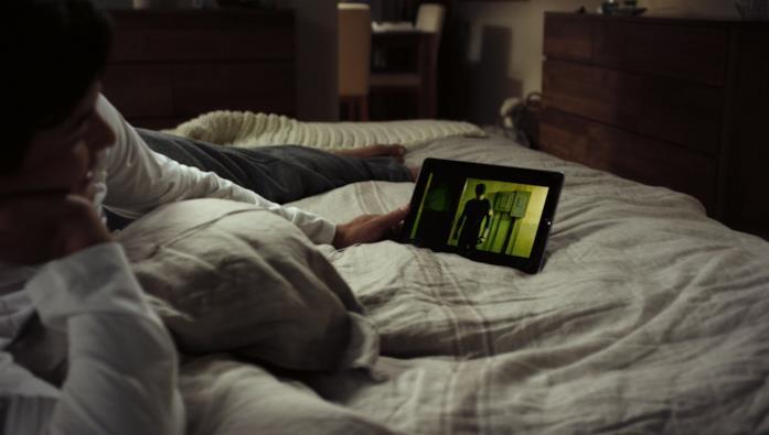Un ragazzo sdraiato sul letto guarda una serie su un tablet