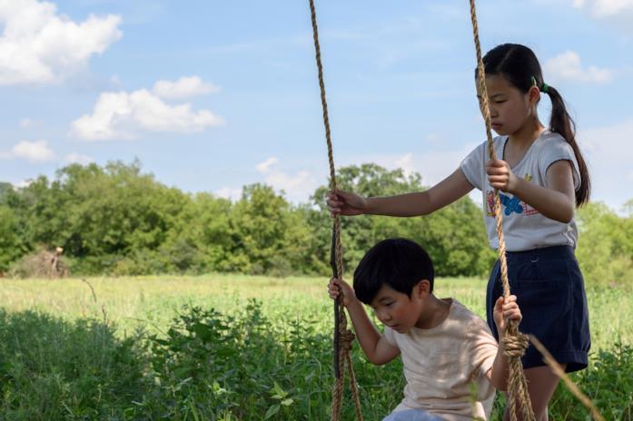 I due figli dei Kim giocano con l'altalena