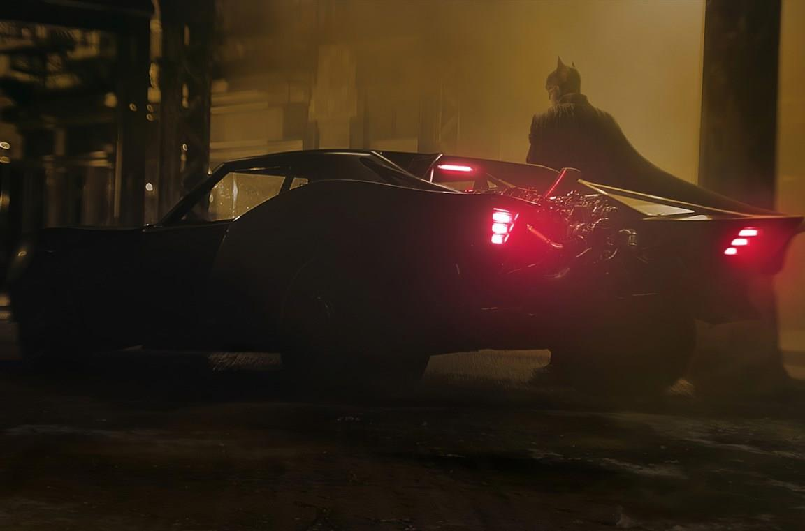 Un'immagine di Batman al fianco della Batmobile