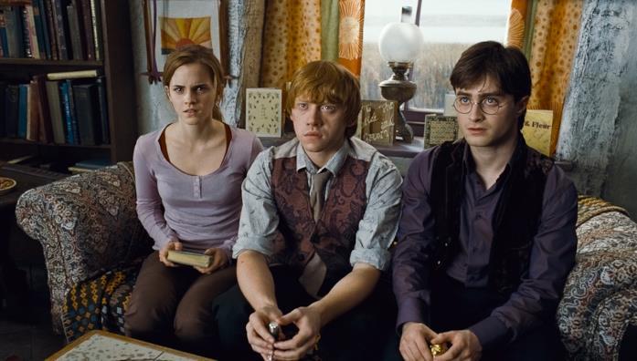 Hermione, Ron e Harry seduti su un divano