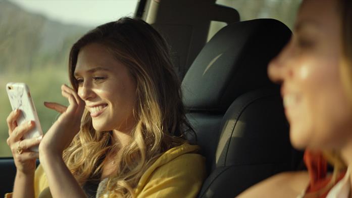 Elizabeth Olsen guarda uno smartphone