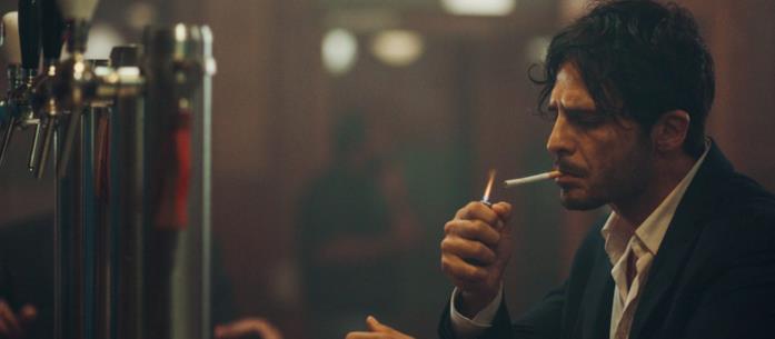 Un uomo fuma una sigaretta al bar