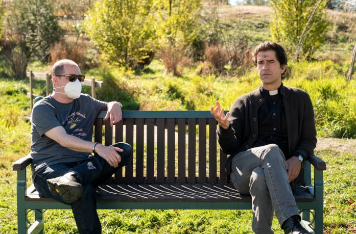 Padre Paul con il regista di Midnight Mass seduti su una panchina