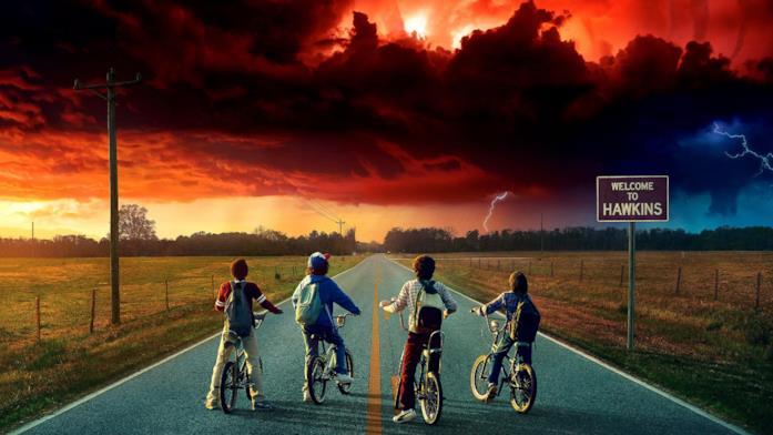Lucas, Dustin, Mike e Will, tutti in bici di fronte a un cielo rosso in un'immagine promozionale di Stranfe