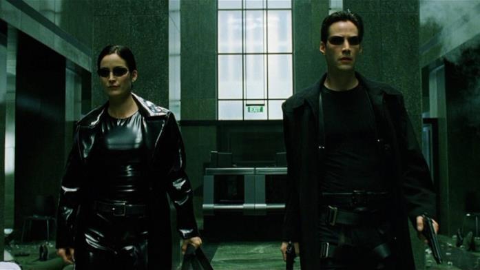 Trinity a sinistra e Neo a destra, entrambi con le pistole in mano