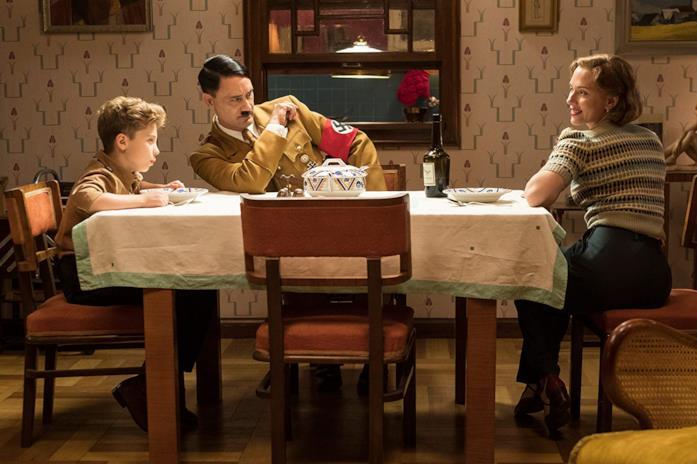 Roman Griffin Davis, Taika Waititi e Scarlett Johansson riuniti a tavola in una scena del film