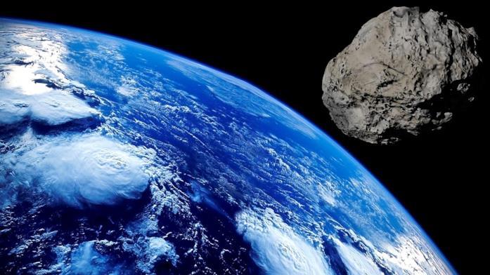 Un'immagine che ritrae un meteorite (a destra) e il pianeta Terra (a sinistra)