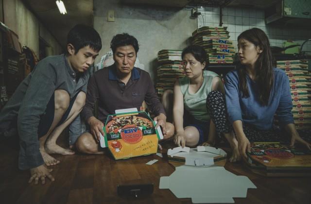 La famiglia Kim piega cartoni della pizza per vivere in una scena di Parasite