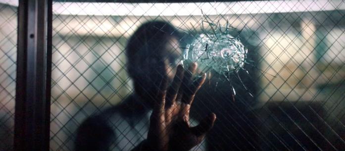 Il protagonista osserva un vetro incrinato da un foro di proiettile