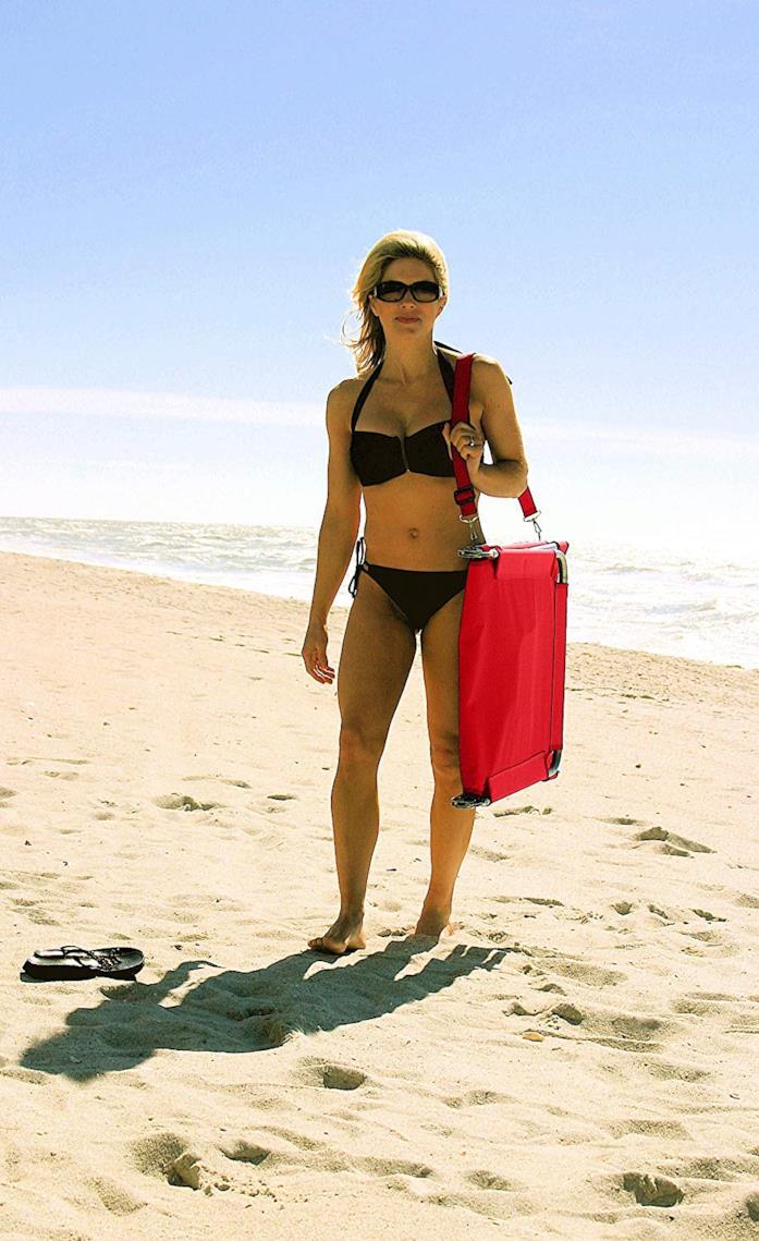 Donna in spiaggia con la sdraio piegata e portata a tracolla