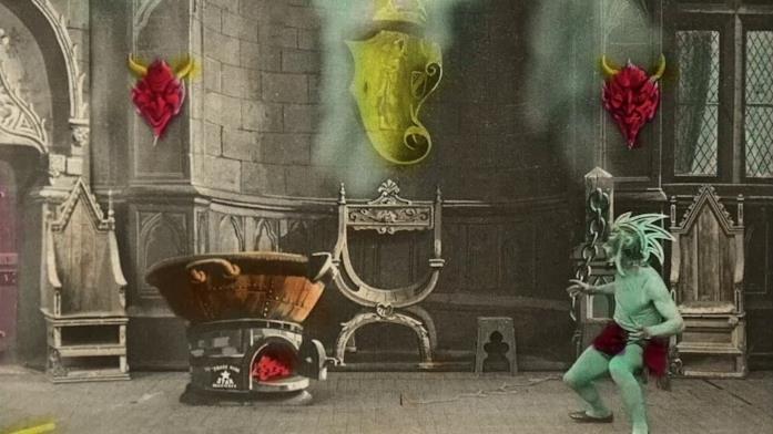 Un satanasso guarda un calderone che bolle in una sala antica. La pellicola in bianco e nero è colorata a mano.