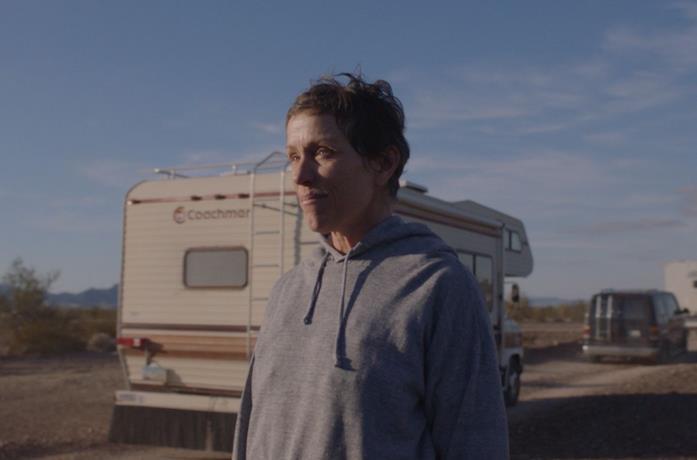 Frances McDormand con un camper alle spalle n una scena di Nomadland