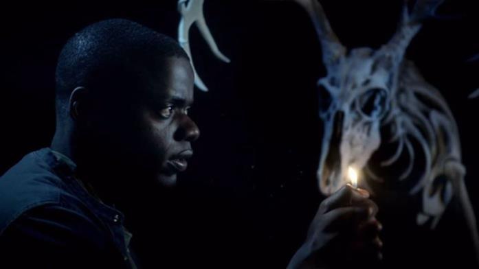 Daniel Kaluuya cammina in un ambente buio con la luce di un accendino