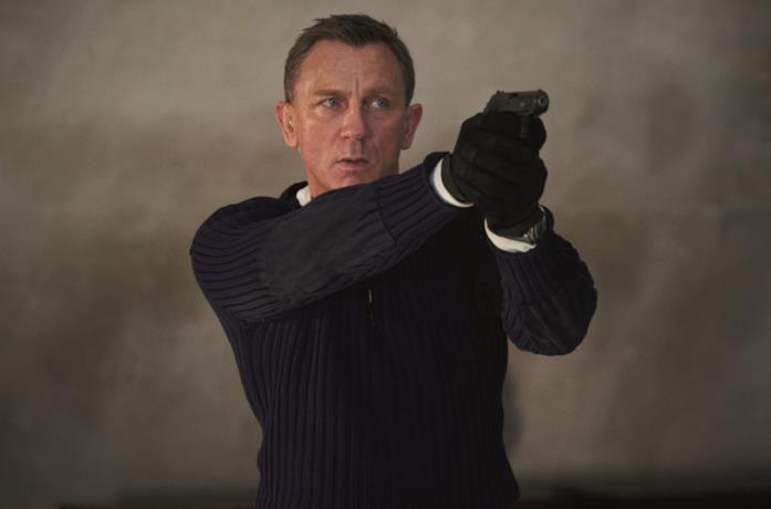 Primo piano di Daniel Craig che impugna una pistola