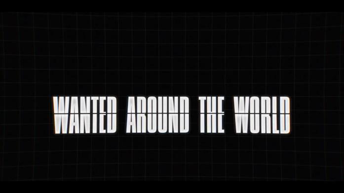 """La frase """"Wanted around the world"""" sopra una sfondo nero"""