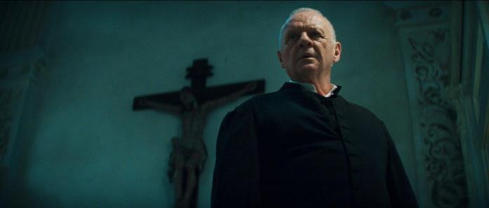 Anthony Hopkins nel ruolo di padre Lucas con un crocifisso alle spalle in una scena di Il Rito