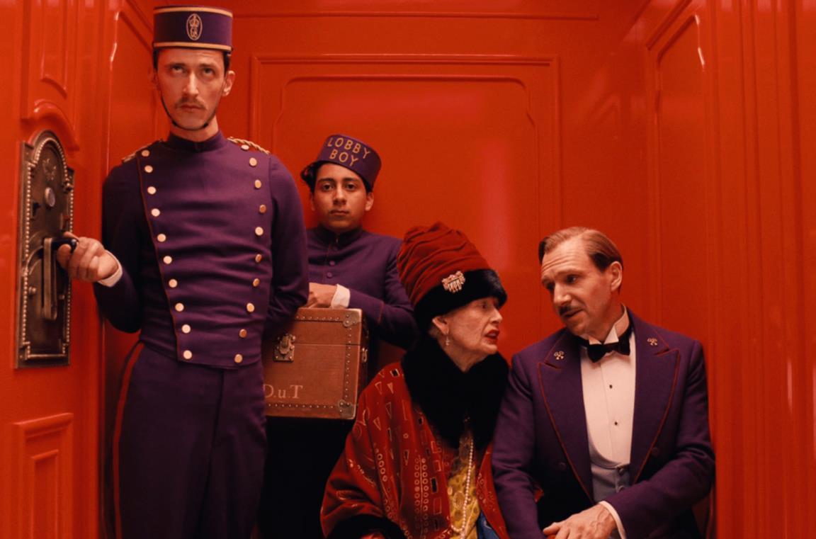 Monsieur Gustave, alcuni dipendenti dell'hotel e una donna usano un ascensore rosso