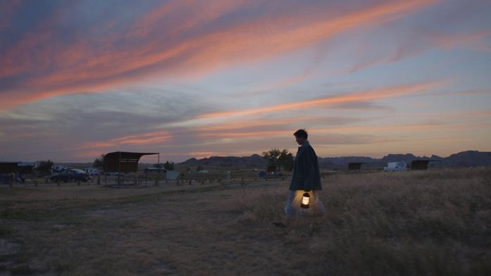 Fern, con una lanterna, cammina in un campo