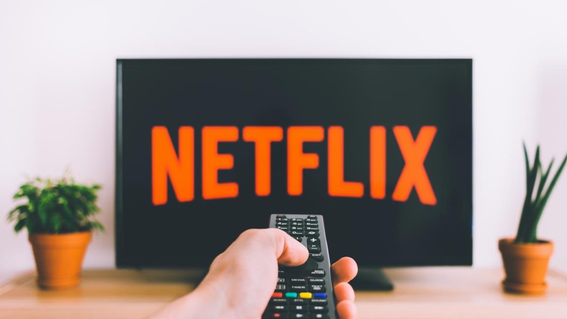 Il logo Netflix in TV e qualcuno con un telecomando in mano