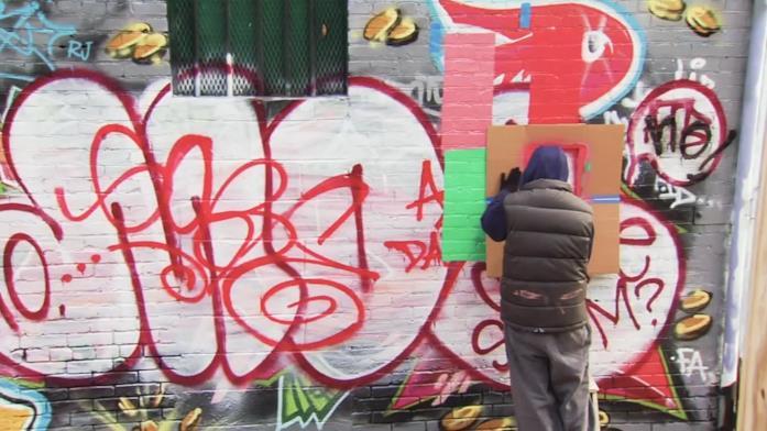 Un misterioso artista sta disegnando qualcosa in un muro