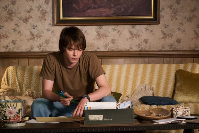 Charlie Heaton nei panni di Jonahtan Byers, seduto sul divano con una penna in mano