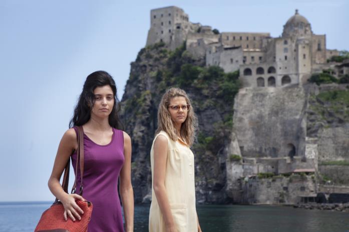 Lila ed Elena guardano la telecamera, sullo sfondo il Castello Aragonese di Ischia