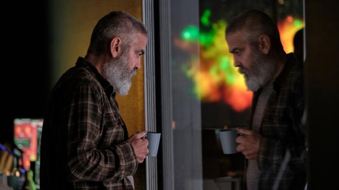 Mezza figura di George Clooney allo specchio con tazza in mano in una scena di The Midnight Sky