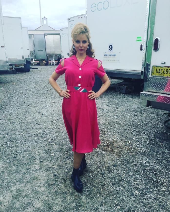 Cara Buono con un vestito viola in un parcheggio su un set
