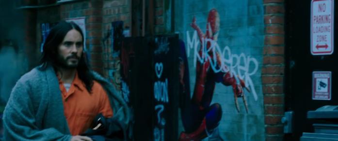 Michael Morbius in primo piano; alle sua spalle un murales dedicato a Spider-Man