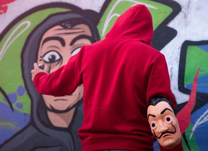 Ragazzo con felpa rossa dipinge murales a tema La Casa di Carta